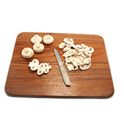 Sliced mushrooms on cutting board with knife