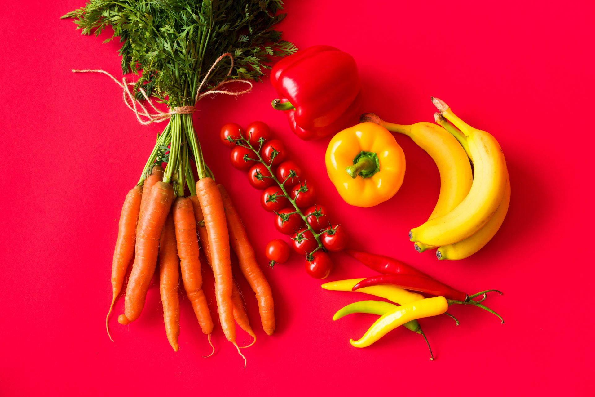 Fresh fruits and vegetables on red background